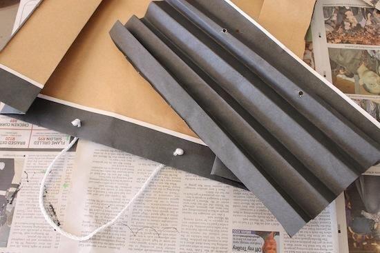 Reutilizamos una bolsa de compras de papel negro para hacer que nuestras alas de murciélago. Papel negro también funcionaría. Acordeón doblar el papel. A continuación, corte el papel doblado a la envergadura de brazo desea que sus bates tengan.