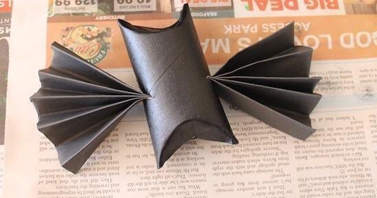 Para adjuntar sus alas de murciélago Haga un corte horizontal a cada lado del cuerpo de su bate en el medio del rollo de papel. A continuación, empuje sus alas acordeón a través de las rendijas y estirarlos para que se abren en abanico muy bien.