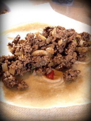 Dorar la carne de vacuno. Agregue las cebollas y los pimientos y cocinar hasta que estén blandas. Splash en algunos de la salsa. Añadir 1/8 de la mezcla a la tortilla.