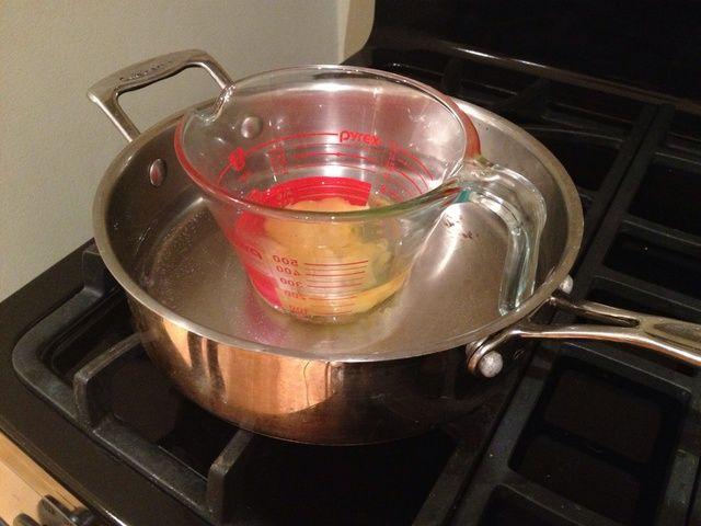Lentamente derretir la cera de abejas y aceite de almendras en un baño María a fuego medio alto. Puede crear una caldera doble, colocando la taza de medir pyrex en una olla con agua.