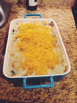 Añadir las patatas y se extendió para cubrir bisontes y queso capas. Cubrir con el queso restante luego hornear por 20 minutos o hasta que estén doradas.