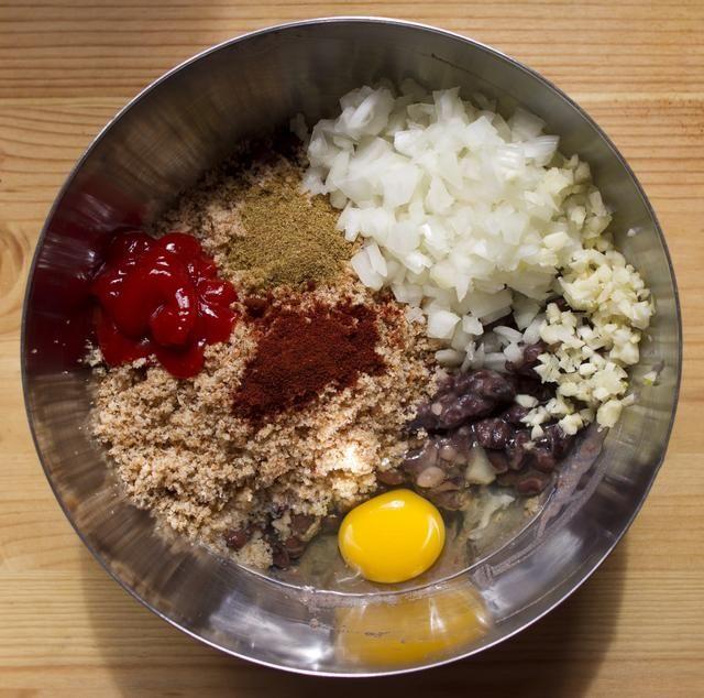 Escurrir los frijoles y poner en un tazón mediano. Frijoles puré hasta media siguen siendo en general. Combine los frijoles, el pan rallado, huevo, Chile en polvo, comino, cebolla, salsa de tomate y el ajo. Condimentar con sal y pimienta.