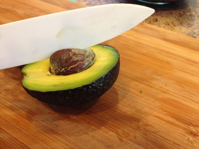 aquí's a trick to get the seed out. Hit the seed with the upper part of your knife. It should stick into the seed then grab the top of the blade just above the seed and wiggle it loose. Toss the seed.