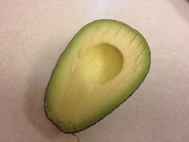 Justo antes de servir añadir un aguacate cortado en cubitos. Hacer una longitud de corte sabia alrededor, pero no a través de la semilla. Gire cada lado y va a partirse. Cortar líneas más abajo la longitud sin perforar la piel.