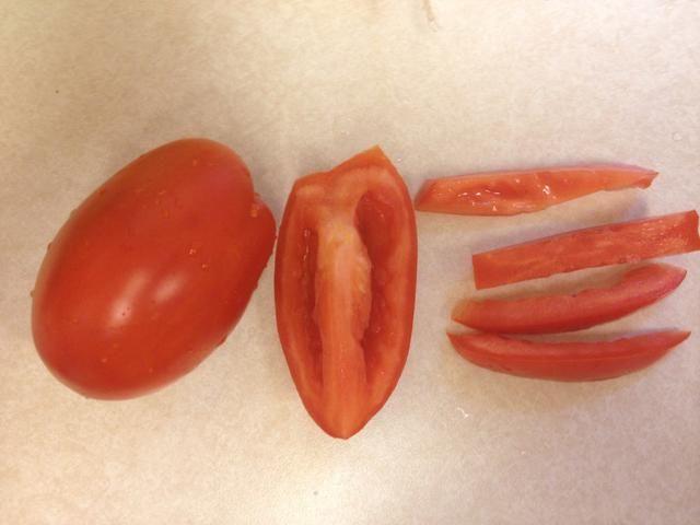 Cortar cada trimestre del tomate en tres o cuatro tiras y ellos dados.
