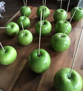 Lavar las manzanas y seque. Pegue pinchos o palos de paleta en la parte superior de la manzana.