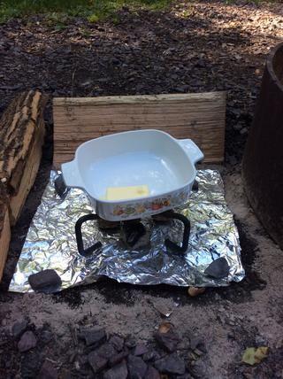 Dado que se creó todo este postre fuera, he creado una pequeña estufa usando carbones calientes y una tapa de hierro fundido de pie para derretir 3/4 barra de mantequilla.