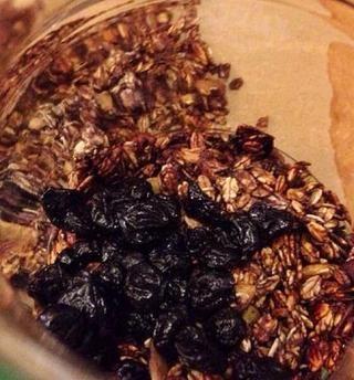 Mover los trozos de granola a un recipiente. Añadir los arándanos secos.