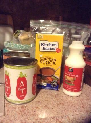 Agregue la leche, puré de tomate y el caldo.