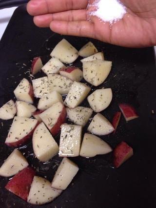Cortar unas patatas de su elección en un gran dado de echar en el aceite de oliva, sal, ajo picado ahumado y hierbas de su elección. Elegí Hierbas de Provence