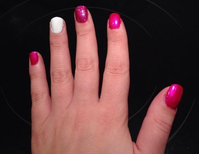 Pintura esmalte de brillo sobre color de rosa en el dedo medio