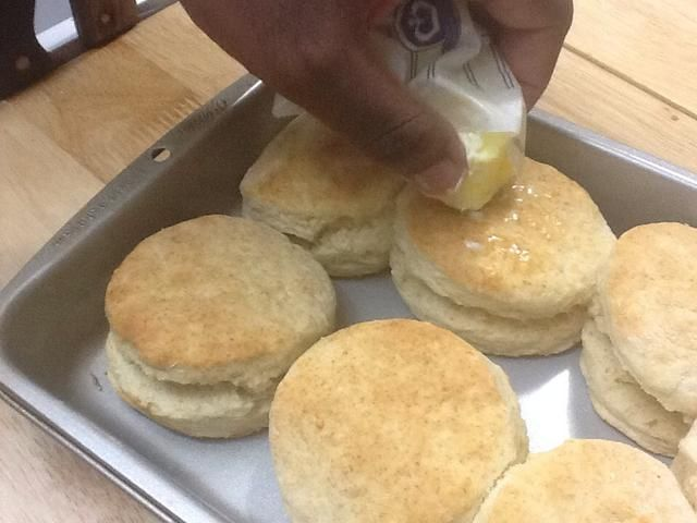Una vez que se hacen las galletas, frote la parte superior con la mantequilla.