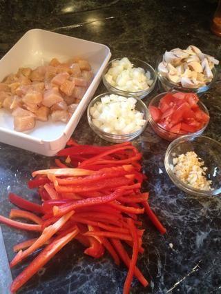 Picar el pollo, pimientos rojos, cebolla, tomates, champiñones. Cortar el ajo.
