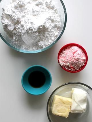 Reunir los ingredientes para helar. Confitero's sugar, 1/4 cup butter, 1/4 cup shortening, 1 tsp vanilla extract, 1/2 tsp peppermint extract, and crushed candy canes.