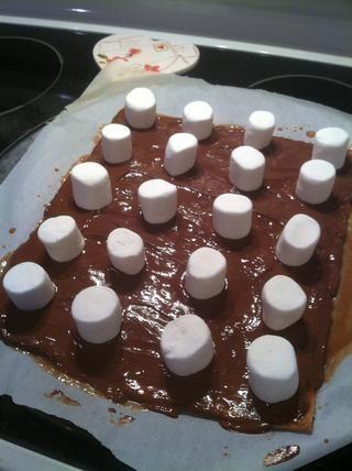 Coloca los grandes malvaviscos en el chocolate en filas.