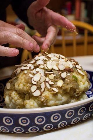 Difundir el resto de la misma sobre la parte superior y los lados de la coliflor. Espolvoree las almendras sobre la parte superior.