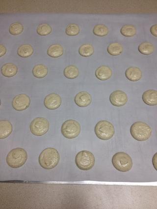 Pipe los macarons en el papel de pergamino en el tamaño que desee. Toque en la bandeja para hornear con firmeza en un contador para aplanar la cookie.