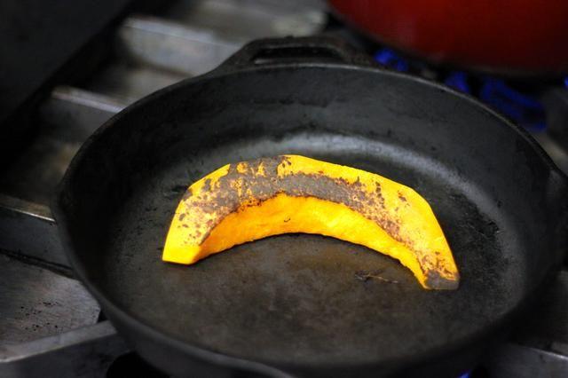 Charlas su calabaza y las zanahorias a fuego medio-alto en una sartén de hierro fundido seco.