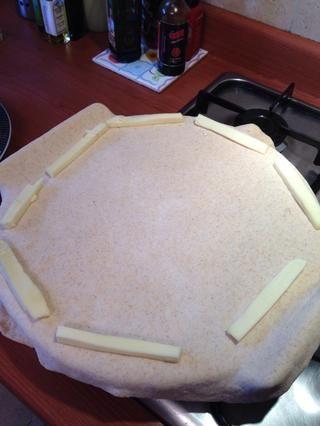 Coloque los palitos de queso alrededor del borde de la pizza