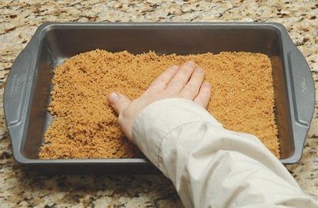 Con los dedos, extender la mezcla de galleta en forma pareja sobre el fondo del molde preparado. Pat la mezcla de miga con firmeza con el dorso de una cuchara.