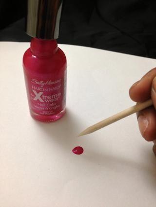 Siguiente apoderarse de su color rosado oscuro y su palillo de dientes. Caída de un poco de pintura en un pedazo de papel y sumergir su palillo para recoger un poco de color. yo'm using Hot Magenta by Sally Hansen.