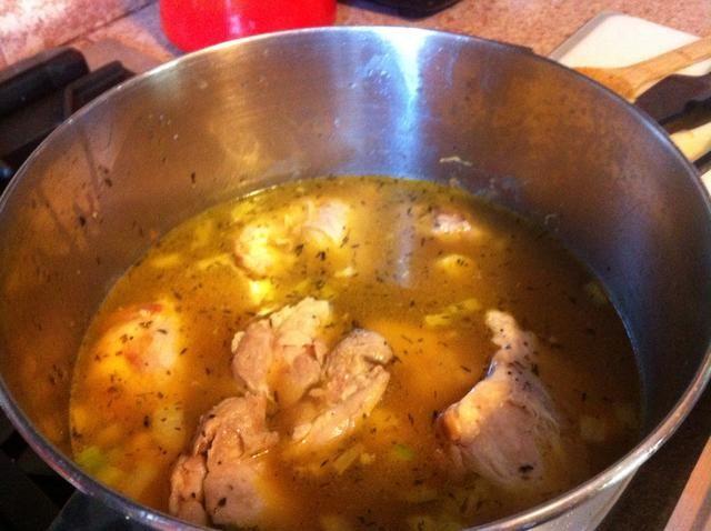 Añadir el caldo de pollo, y el lugar muslos de pollo de nuevo en la olla. Llevar a ebullición, tapar y bajar el fuego a medio-bajo. Cocine por 30 minutos.