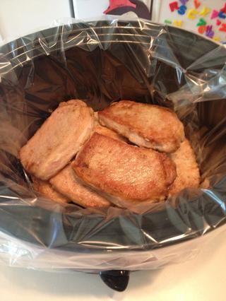 Repita el proceso para todas las chuletas de cerdo. Añadir a la olla de cocción lenta cuando se enfríe lo suficiente como para manejar. Me gusta usar bolsas hechas específicamente para la olla eléctrica para una fácil limpieza.