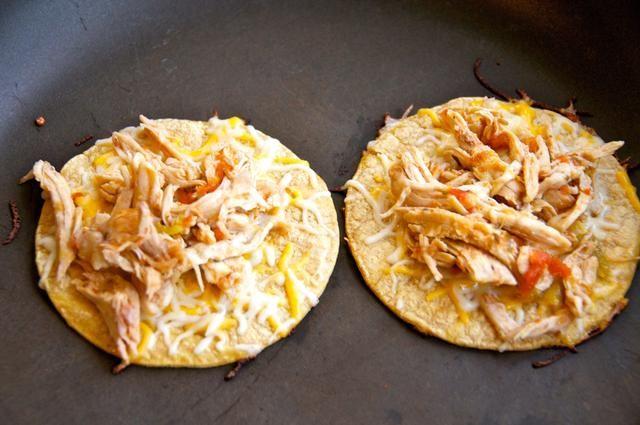 Dorar la tortilla por ambos lados a continuación, coloque un poco de queso y cerca de 1/4 taza de pollo desmenuzado en la parte superior. Deje que el queso se derrita antes de retirar de la sartén.