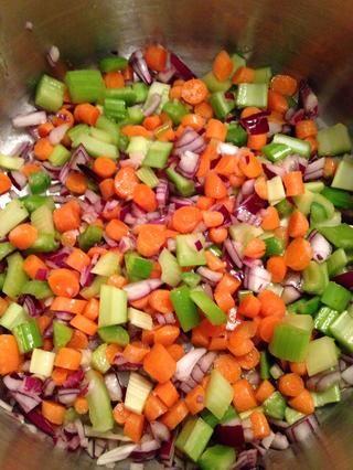 Una vez que los calores de aceite de oliva, añadir el ajo, las zanahorias, el apio, y cebolla roja. Revuelva y cocine por unos 5 minutos hasta que empiecen a ablandarse.