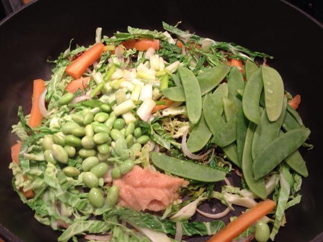 Añadir las verduras, que son más rápidos para cocinar por ejemplo, frijoles edamame (soja), tirabeques y cebolla de primavera