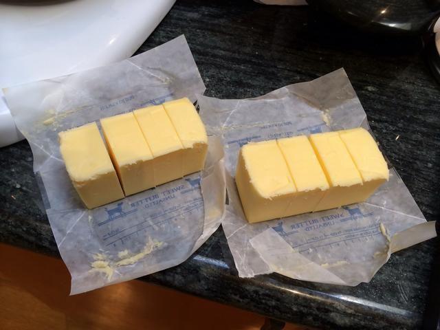 Cortar 2 barras de mantequilla temperatura ambiente en trozos más pequeños.