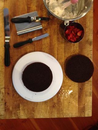 A continuación, corte cada pastel por la mitad y la pila de su pastel, llenando las fresas en entre cada capa.