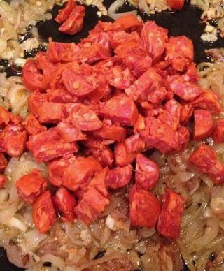 Agregue el chorizo a la chalota y el ajo. Revuelva y cocine el chorizo de unos 10 minutos.