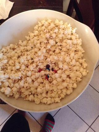 Vierta la bolsa de palomitas y una bolsa de M & M's into a large bowl and mix.