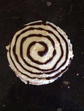 Pipe un patrón de remolino con el jarabe de chocolate en otra magdalena helada.