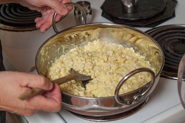 Cuando las semillas de comino comienzan a chisporrotear y cambiar de color, añadir en la mezcla de maíz y el turmeric.Mix juntos también.