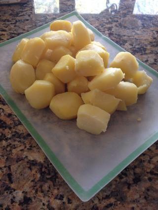 Mientras que las verduras se cocinan abajo, pelar y cortar las patatas y se sientan a un lado