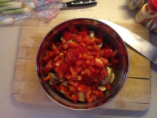Cortar el pimiento en trozos pequeños y en el recipiente con las cebollas verdes y champiñones.