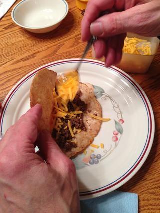 En la mesa justo antes de comer, nos cuchara en el queso cheddar rallado y lechuga. También puede agregar los tomates frescos cortados en cubitos, salsa, lo que sea.