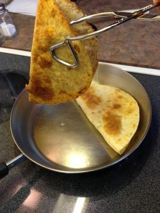 Levante con cuidado, manteniendo la tortilla doblada. Deje el exceso de goteo de aceite en la cacerola