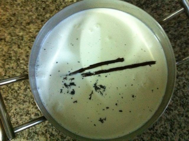 Agregue los frijoles y vainas en una olla de acero inoxidable junto con la nata y la leche. Corté cada mitad de la vaina de vainilla por la mitad transversalmente por lo que encajaría en el bote. Calentar suavemente a fuego lento.