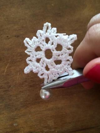 Usando sus alicates, envuelva el exceso de alambre alrededor para formar un bucle. Cadena de la perla a través del punto inferior si el copo de nieve. Usando los alicates, cerrar el círculo alrededor de la base del copo de nieve.