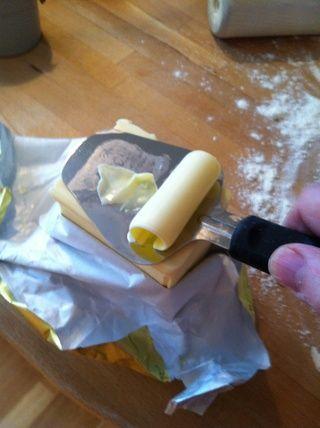 Afeitarse la mantequilla fría rápida y colocar rodajas sobre la masa. He encontrado que es práctico usar sólo una máquina de cortar normal de queso para la mantequilla fría.