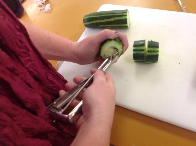 Utilice el melón y retire las semillas, asegurándose de no cortar todo el camino a través del pepino. Deja un pequeño fondo en el pepino para mantener el relleno.