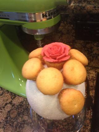 Tome la magdalena y tubo de glaseado rosa y luego vuelva a colocar en la pelota