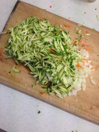 Rallar los calabacines y las zanahorias. Finamente trocea la cebolla.