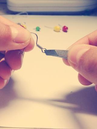 Poner las pinzas / alicates dentro del bucle de la parte inferior del aro pendiente (la parte que irá en el oído)