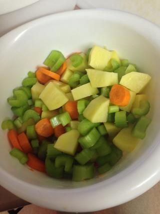 Picar las zanahorias, el apio y las patatas.