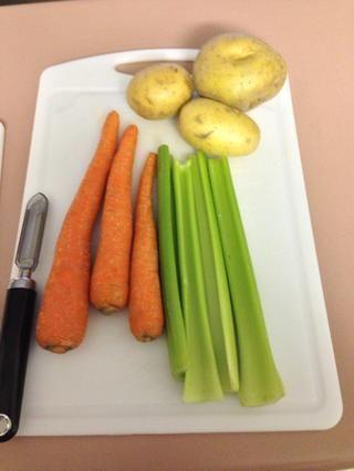 Organizar las zanahorias, las patatas y el apio en una tabla de cortar con el pelador de verduras.