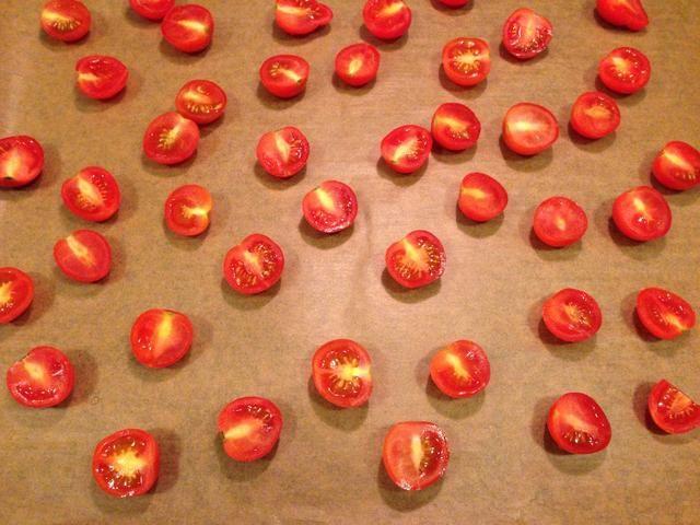 Cortar los tomates y colocarlos en una bandeja para hornear.